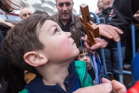 retrieved: Thessaloniki, Greece, January 6, 2016: A child kisses a wooden cross retrieved from the sea during the blessing of the water ceremony marking the Orthodox Epiphany Day