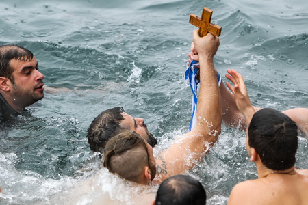 retrieved: Thessaloniki, Greece, January 6, 2016: A swimmer kisses a wooden cross retrieved from the sea, during the blessing of the water ceremony marking the Orthodox Epiphany Day, in port of Thessaloniki