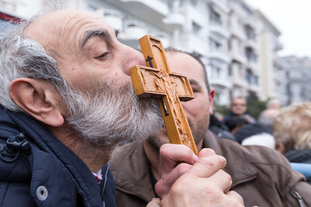 retrieved: Thessaloniki, Greece, January 6, 2016: A man kisses a wooden cross retrieved from the sea during the blessing of the water ceremony marking the Orthodox Epiphany Day