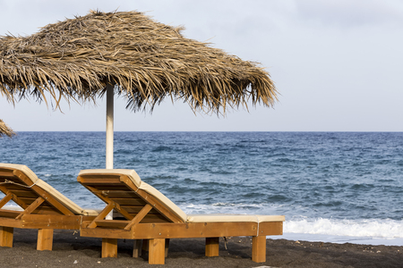 sunbeds: view of Perissa beach on the Greek island of Santorini with sunbeds and umbrellas. Beach is covered with fine black sand, and drops off sharply into the water. Stock Photo