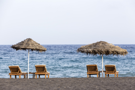 sharply: view of Perissa beach on the Greek island of Santorini with sunbeds and umbrellas. Beach is covered with fine black sand, and drops off sharply into the water. Stock Photo