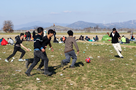 fille pleure: Polykastro, Gr�ce, le 7 F�vrier, 2016: Migrants et r�fugi�s jouer au football dans le stationnement d'une station d'essence � Polykastro comme attendant de traverser la fronti�re pour ARY de Mac�doine �ditoriale