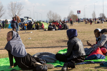 Polykastro, Greece, February 7, 2016: Thousands migrants and refugees are waiting in the parking lot of a gas station in order to cross the borders to FYR of Macedonia Editorial