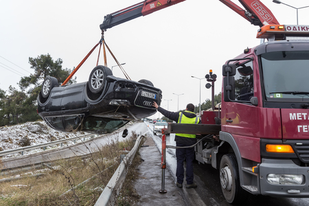 Thessaloniki, Greece - January 18, 2016: Man towing damaged car over a tow truck on the side of the road in Thessaloniki, Greece.