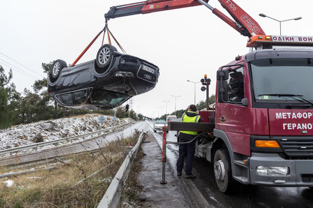 thessaloniki: Thessaloniki, Greece - January 18, 2016: Man towing damaged car over a tow truck on the side of the road in Thessaloniki, Greece.