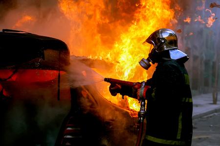 Athen, Griechenland - 4. Februar 2016: Feuerwehrmänner eine brennende Auto nach einer Explosion kämpfen