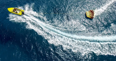 ios: Ios, Greece - September 19, 2015: Tourists having fun on inflatable watercraft boat at the beautiful ocean of Greek island of Ios island, Cyclades, Greece. Editorial