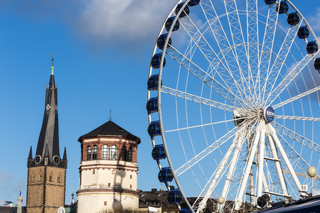 rhine westphalia: Dusseldorf, Germany - December 8, 2015: St Lambertus church is Roman Catholic church in Dusseldorf historic center with Luna park attraction in Dusseldorf, Germany. Editorial