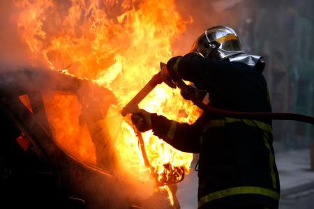 peleando: Atenas, Grecia - 4 de febrero 2016: bomberos luchando contra un coche en llamas despu�s de una explosi�n Editorial