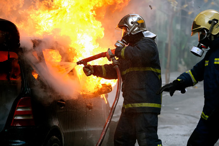peleando: Atenas, Grecia - 4 de febrero 2016: bomberos luchando contra un coche en llamas después de una explosión Editorial