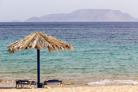 sunbeds: Blue sea, golden sand, sunbeds and umbrellas on the beach. Ios island, Greece Stock Photo