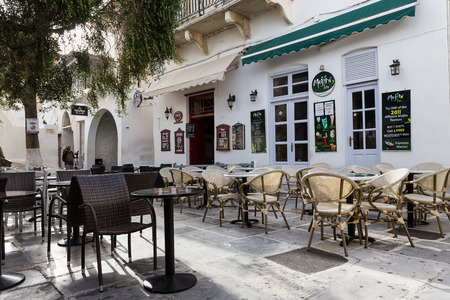 ios: Ios, Greece - September 19, 2015: Empty tables in greek coffee shop on the street of mediterranean island Ios, Greece. Editorial