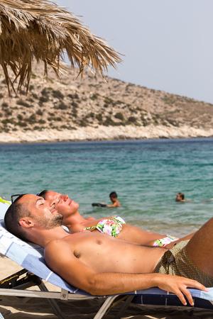 ios: Ios, Greece - September 19, 2015: Tourists sunbathing at the beach of Ios Greek island, in Cyclades. Editorial