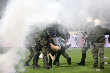 riots: Thessaloniki, Greece - March 02, 2016: PAOK fans getting arrested after clashing with riot police during the semifinal Greek Cup game between PAOK and Olympiacos played at Toumba stadium
