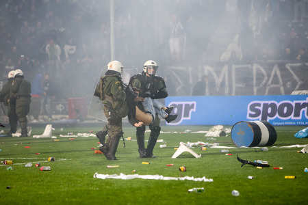 violent: Thessaloniki, Greece - March 02, 2016: PAOK fans getting arrested after clashing with riot police during the semifinal Greek Cup game between PAOK and Olympiacos played at Toumba stadium