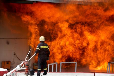 Aspopirgos, Griechenland - 28. März 2016: Feuerwehrmänner kämpfen, um das Feuer zu löschen, die in einer Lackfabrik brach