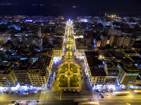 taken: Aerial view of Aristotelous Square and the northern Greek city Thessaloniki at night. Image taken with action drone camera causing distortion and blur.