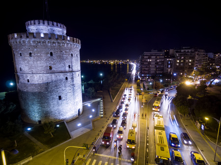 action blur: Aerial view of famous White Tower and the city of Thessaloniki at night, Greece. Image taken with action drone camera causing distortion and blur.