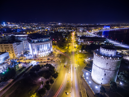 thessaloniki: Thessaloniki, Greece - January 13, 2016: Thessaloniki, Greece - January 29, 2016: Aerial view of famous White Tower and the city of Thessaloniki at night, Greece. Image taken with action drone camera causing distortion and blur.