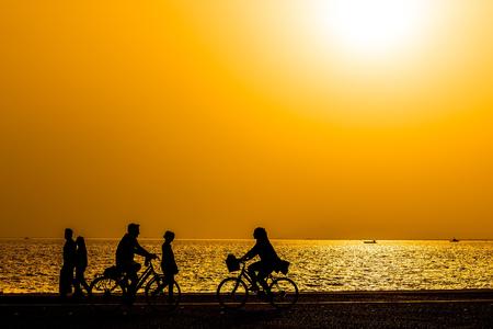 Silhouetten von Menschen einen Spaziergang am Meer von der Stadt bei Sonnenuntergang genießen