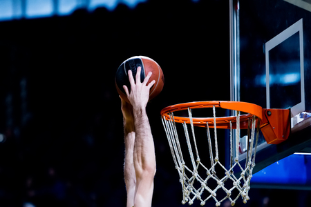 undefined: Thessaloniki, Greece - December 19, 2015: Undefined player hands throwing a ball through the net  during the Greek Basket League game Aris vs Panathinaikos