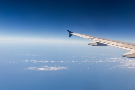 Wing of airplane flying above the clouds in the sky Stock Photo