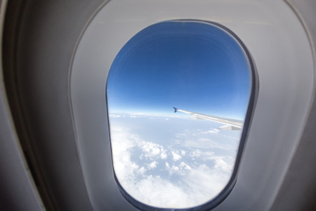 sidelight: airplane window with wing and cloudy sky behind. Picture taken with fisheye lens Stock Photo