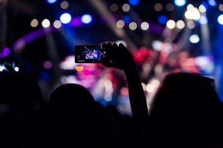 Mano con unos registros de teléfonos inteligentes festival de música en vivo, Tomar la foto de la etapa del concierto, concierto en vivo, festival de música, juventud feliz, partido de lujo, exterior paisaje. facebook vivo. Foto de archivo