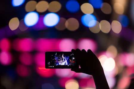 Hand with a smartphone records live music festival, Taking photo of concert stage, live concert, music festival, happy youth, luxury party, landscape exterior. facebook live.