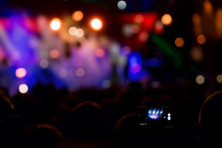Hand with a smartphone records live music festival, Taking photo of concert stage, live concert, music festival, happy youth, luxury party, landscape exterior