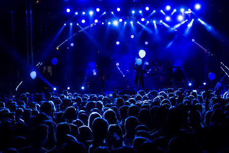 silhouettes of concert crowd in front of bright stage lights. motion image