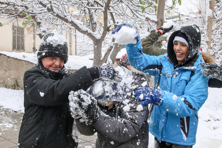 palle di neve: Thessaloniki, Greece - November 30, 2016: Boys and girls play with snowballs in Thessaloniki