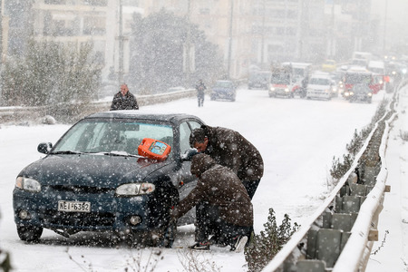 heavy chains: Thessaloniki, Greece - January 10, 2017: Drivers are trying to install chains on their tyres under heavy snow storm. Editorial