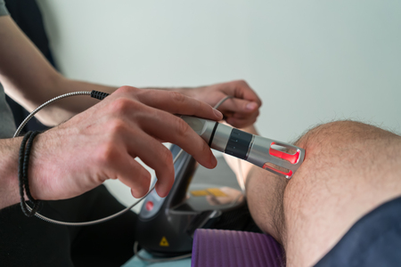 back link: Laser therapy on a knee used to treat pain. selective focus