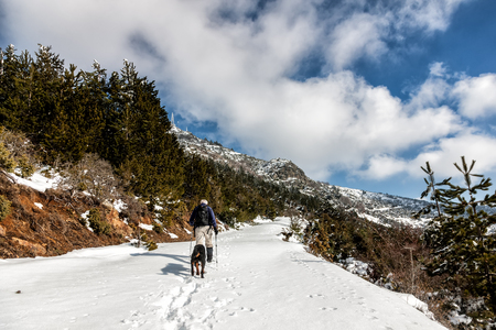 unknown man party with his dog walking in a snowy landscape in northern Greece