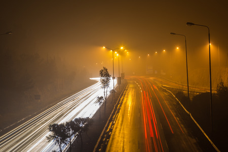 Speed Traffic - light trails on motorway highway at night with fog, long exposure abstract urban background Stock Photo