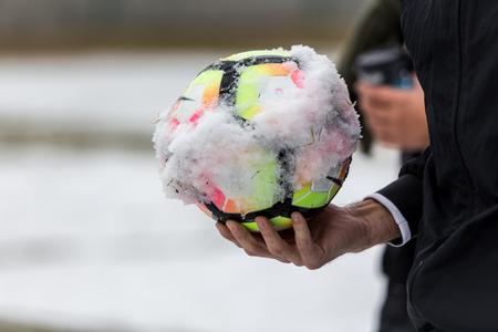 Thessaloniki, Greece - January 14, 2017: closeup of snowy soccer ball and the referees hand before the match Iraklis vs Corfu at Kaftatzoglio stadium