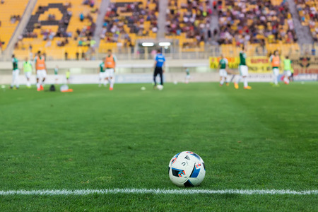 striker: Thessaloniki, Greece - September 3, 2016: Soccer ball in the foreground and blurred players in backraount before the match Aris vs Panathinaikos at Charilaou stadium Editorial