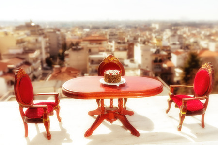 diner time. miniature classical dining on a marble floor, background of blurred houses. image cross processed for vintage look Stock Photo