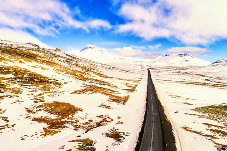 Aerial view of road and snowy mountains, Iceland.  image cross processed for vintage look
