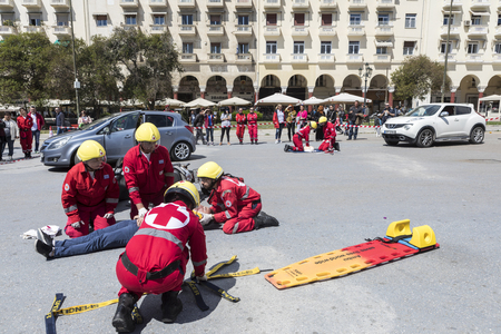 rescuing: Thessaloniki , Greece - April 9, 2017: First aid, victim liberation in an car accident and helmet removal demonstration by the Hellenic Red Cross rescue team Editorial