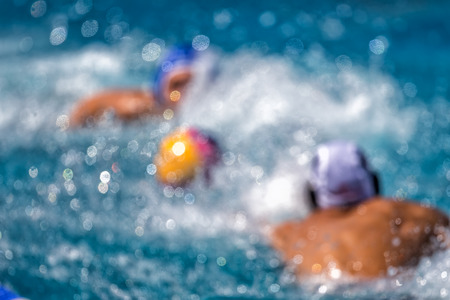 Blurred players of the two teams in action during the water polo game  Stock Photo