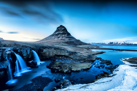 Spring sunrise over the famous Kirkjufellsfoss Waterfall with Kirkjufell mountain in the background in Iceland Stock Photo