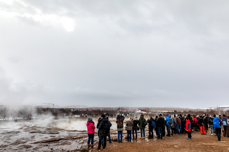 Geysir, Iceland - March 24, 2017: people are waiting for fountain geyser to erupt at Strokkur geyser. Strokkur is one of the most famous fountain geyser in Iceland.