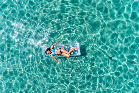 aerial view  of a beautiful young woman in bikini on a matress in the sea