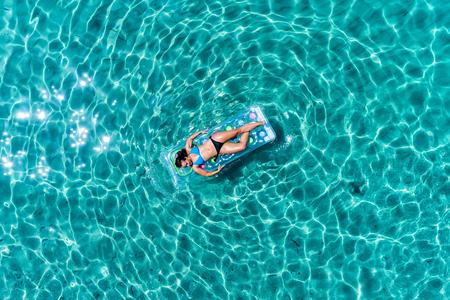 Luchtfoto van een mooie jonge vrouw in bikini op een matras in de zee Stockfoto - 83206265