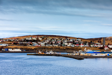 Husavik, Iceland - March 29, 2017: Beautiful view of the historic town of Husavik with traditional houses and traditional fisherman boats lying in the harbor, northern coast of Iceland Editorial