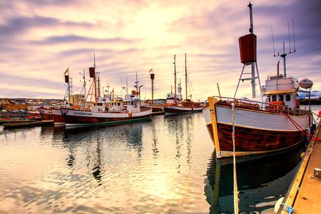 Husavik, IJsland - 29 maart 2017: Traditionele walvis kijken boten liggend in de haven van Husavik in gouden avondlicht bij zonsondergang, noordelijke kust van IJsland