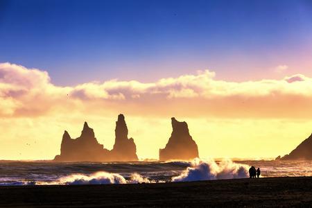 Colorful sunset on basalt rock formations Troll toes on black beach. Reynisdrangar, Vik, Iceland