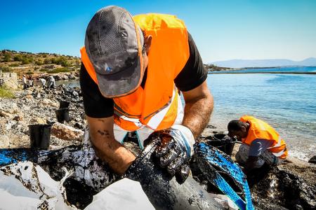 サラミス、アテネ、ギリシャ-9 月13、2017: 古いタンカーがサラミス島の近くで沈没した後に、アテネ近郊のサラミス島のビーチで、海岸に洗われた油